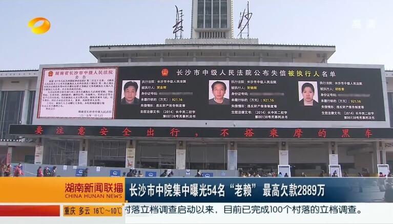Ekran wstydu w mieście Changsha, na którym wyświetlane są zdjęcia i dane chińskich dłużników. Fot. screenshot CNN